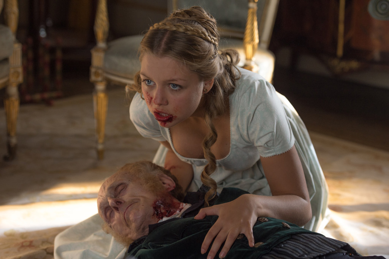 Annabelle (Jess Radomska) chewing her grandfather in Screen Gems' PRIDE AND PREJUDICE AND ZOMBIES.